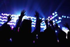 Das Publikum, das einen Felsen aufpasst, Hände in der Luft zu zeigen, hintere Ansicht, Stadium beleuchtet Lizenzfreie Stockfotos