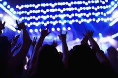 Das Publikum, das einen Felsen aufpasst, Hände in der Luft zu zeigen, hintere Ansicht, Stadium beleuchtet Lizenzfreies Stockfoto
