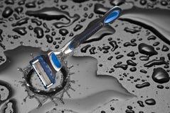 Rasieren des Rasiermessers innerhalb eines Tropfens des Wassers Lizenzfreies Stockfoto