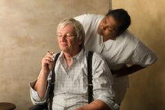 Das Rauchen des alten Mannes wird gefasst Stockfotos