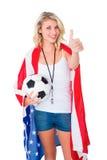 Das recht blonde Fußballfan, das USA trägt, kennzeichnen Daumen sich zeigen Stockfoto