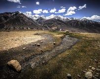 Das reißender Fluss im Tal und in den Schnee-mit einer Kappe bedeckten Spitzen des moun Lizenzfreie Stockbilder