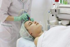 Das Reiben der Haut des Gesichtes wird von einem Cosmetologist in einem Sch?nheitssalon erfolgt lizenzfreie stockbilder