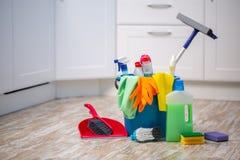 Das Reinigungskonzept mit Versorgungen Reinigungsfrau, die das Reinigungsspray-Flaschenschießen glücklich und das Lächeln zeigt lizenzfreies stockfoto