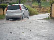 Das Reisen auf nasses Raod nach einer Regenguss-Aufgabe archiviert stockbilder