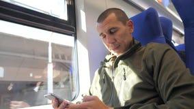 Das Reisendmannunbekannte, das am Fenster Smartphone von mittlerem Alter im U-Bahnbahnzug sitzt, schreibt sms zum Social Media stock video