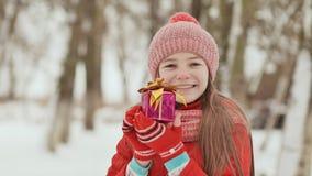 Das reizend junge Schulmädchen hält froh in ihren Händen einen verpackten Kasten mit einem Geschenk im Winterwald herein stock footage