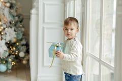 Das reizend Kleinkind des kleinen Jungen, das nahe einem Fenster mit einem Gi steht Stockfoto