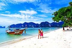 Das reizende Gehen der Paare und Entspannung auf weißem Sandstrand und Boot des langen Schwanzes mit Hintergrund des blauen Himme Stockbild