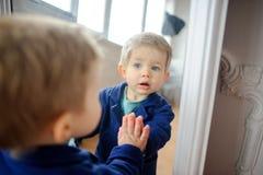 Das reizende Kind schaut in einem Spiegel Lizenzfreie Stockfotografie