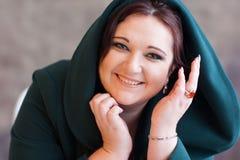 Das reizende Lächeln der überladenen attraktiven Frau Stockfoto