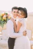 Das reizende Nahaufnahmeporträt der glücklichen umarmenden nelyweds Die Braut mit dem roten Lippenstift hält den Blumenstrauß von lizenzfreie stockfotos