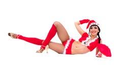 Das reizvolle Mädchen, das Weihnachtsmann trägt, kleidet Lügen Stockfotos