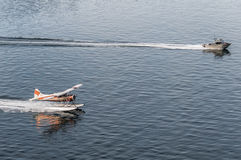 Das Rennen ist mit einem Boot und einer Fläche eingeschaltet Stockfotos