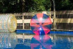 Das riesige Plastikzorbing steigt das Schwimmen auf Wasser im Park im Ballon auf Stockfotografie