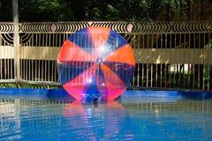 Das riesige Plastikzorbing steigt das Schwimmen auf Wasser im Park im Ballon auf Stockfotos