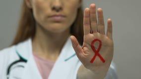 Das rote Band, das auf Doktorhand gemalt wird, stoppen Aids-Epidemie, Verhinderung und Steuerung stock video footage