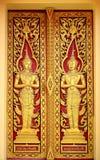 Das rote goldene thailändische Tempeltor-Engelsmuster Stockfotos