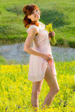 Das rothaarige Mädchen auf Wiese mit gelben Blumen und einem Lächeln Stockbild