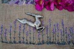Das Rotwild springt auf eine Stickerei von Blumen eines Lavendels lizenzfreie stockfotos