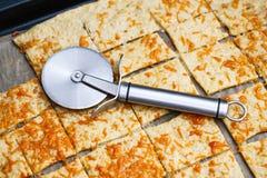 Das runde Messer der Pizza, das vom Edelstahl hergestellt wurde, setzte an Käse cracke Stockbilder