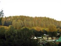 Das russische Dorf befindet sich zwischen den Hügeln Stockfotografie