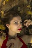 Das russische Mädchen, das auf dem Hintergrund von Wäldern aufwerfen und die Natur im Herbst parken Feiertag, rotes Kleid, Leiden Lizenzfreie Stockfotografie
