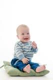 Das Säuglingslächeln des süßen Jungen sitzen auf dem grünen Kissen, das auf weißem b lokalisiert wird stockfoto