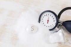 Das Salzverbrauchen kann Blutdruck, Stapel erhöhen des Salzes, Blutdruckmesser auf ecg Aufzeichnung Lizenzfreie Stockbilder