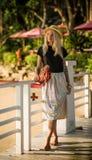 Das schöne blonde Gehen auf den Morgenstrand mit Gelb verlässt in ihren Händen Trägt einen Strohhut, einen langen Rock und ein sc Stockfotografie