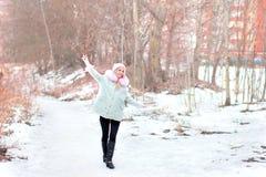 Das schöne blonde Gehen durch den Schnee, freut sich, Hand oben, lo Stockbild