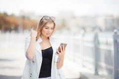 Das schöne blonde Mädchen, das auf dem Damm des Flusses mit dem Telefon steht, liest die Mitteilung Lizenzfreies Stockfoto