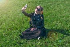 Das schöne blonde Mädchen, das auf einem grünen Rasen sitzt und macht selfie Lizenzfreie Stockfotografie