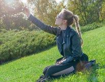 Das schöne blonde Mädchen, das auf einem grünen Rasen sitzt und macht selfie Lizenzfreies Stockbild