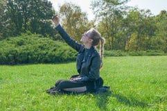 Das schöne blonde Mädchen, das auf einem grünen Rasen sitzt und macht selfie Stockfotografie