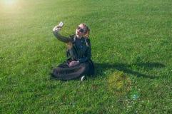 Das schöne blonde Mädchen, das auf einem grünen Rasen sitzt und macht selfie Stockbilder