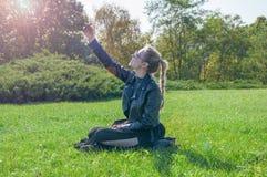 Das schöne blonde Mädchen, das auf einem grünen Rasen sitzt und macht selfie Lizenzfreies Stockfoto