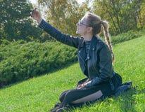 Das schöne blonde Mädchen, das auf einem grünen Rasen sitzt und macht selfie Lizenzfreie Stockfotos