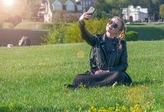 Das schöne blonde Mädchen, das auf einem grünen Rasen sitzt und macht selfie Stockbild