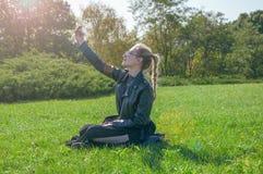 Das schöne blonde Mädchen, das auf einem grünen Rasen sitzt und macht selfie Stockfoto