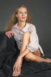 Das schöne blonde Mädchen, das auf einem Teppich sitzt Stockfotos