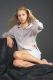 Das schöne blonde Mädchen, das auf einem Teppich sitzt Lizenzfreies Stockbild