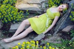 Das schöne blonde Mädchen, das unter dem Frühling liegt, blüht Stockbilder