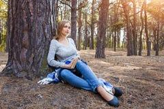 Das schöne blonde Mädchen, das im Frühjahr stillstehen oder der Herbstwald lasen Buch und das Sitzen mit einem Buch Überzeugte ka Stockfoto