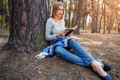 Das schöne blonde Mädchen, das im Frühjahr stillstehen oder der Herbstwald lasen Buch und das Sitzen mit einem Buch Überzeugte ka Stockfotos