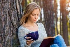Das schöne blonde Mädchen, das im Frühjahr stillstehen oder der Herbstwald lasen Buch und das Sitzen mit Tasse Tee und Buch überz Stockfotografie