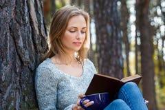 Das schöne blonde Mädchen, das im Frühjahr stillstehen oder der Herbstwald lasen Buch und das Sitzen mit Tasse Tee und Buch überz Lizenzfreies Stockfoto