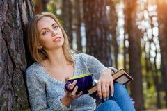 Das schöne blonde Mädchen, das im Frühjahr stillstehen oder der Herbstwald lasen Buch und das Sitzen mit Tasse Tee und Buch überz Stockbilder