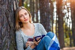 Das schöne blonde Mädchen, das im Frühjahr stillstehen oder der Herbstwald lasen Buch und das Sitzen mit Tasse Tee und Buch überz Lizenzfreie Stockbilder