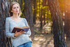 Das schöne blonde Mädchen, das im Frühjahr stillstehen oder der Herbstwald lasen Buch und Stellung Überzeugte kaukasische junge F Lizenzfreies Stockfoto